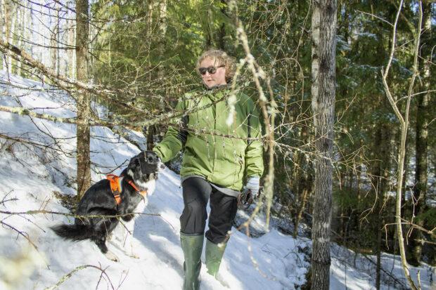 Outi Pylkki ja koira metsässä